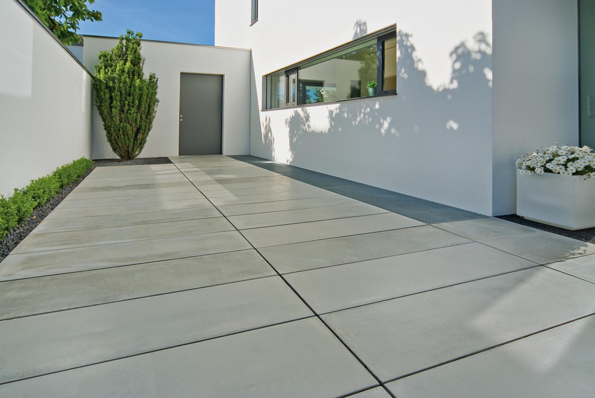 Grau Gepflasterter Hauseingang Aus Sichtbeton Eingerahmt Von Bepflanztem  Kieselbeet Mit Buchsbaumtanne Vor Weißem Haus Und Grauer