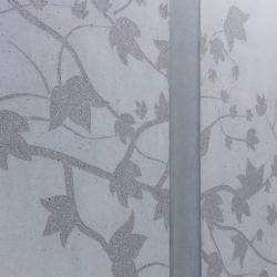 Raumteiler aus Sichtbeton in hellgrau mit Blumenranken und Blaetter und Blumenmuster und Voegeln