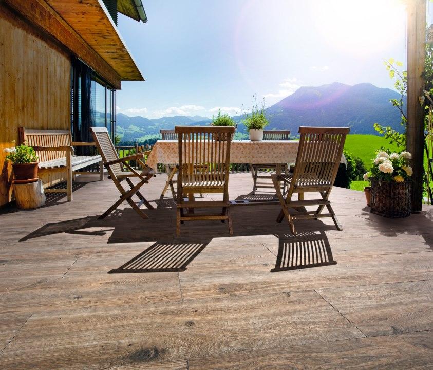 Gepflasterter Steinboden aus großformatigen Feinsteinzeugplatten Carmino 120x40 cm in Eichenoptik auf Terrasse mit Tisch und Blumen und Wiese und Stuehlen und Tischdecke und Sitzbank und mit Ausblick und Berge und Sonne