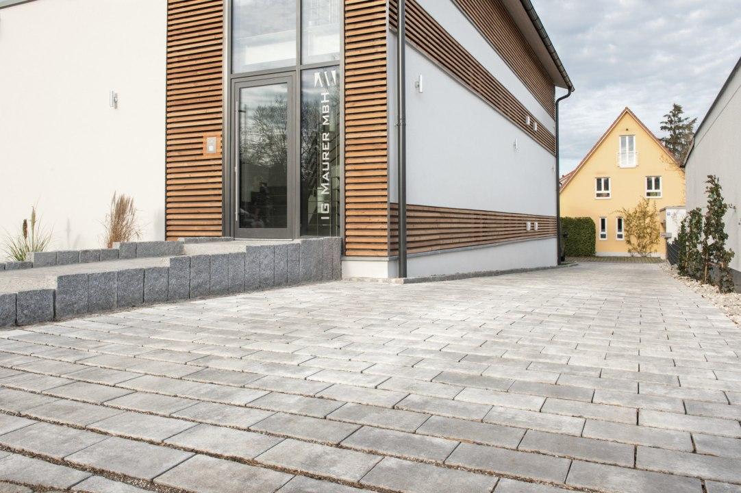 Gepflasterte Einfahrt Steinmauer vor weißem Haus mit Glastuere und Holzverkleidung am Haus und gepflasterter Hauseingang und Haus und Himmel und Pflanzen und weiße Wand
