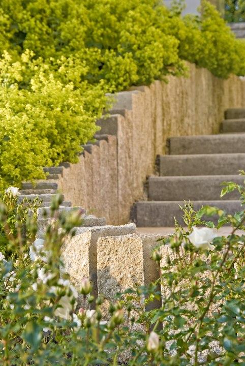 Gepflasterte Sandsteinmauer als Treppenalage und Beeteinzaeunung mit gepflasterter Treppe in Sandsteinoptik mit Pflanzen