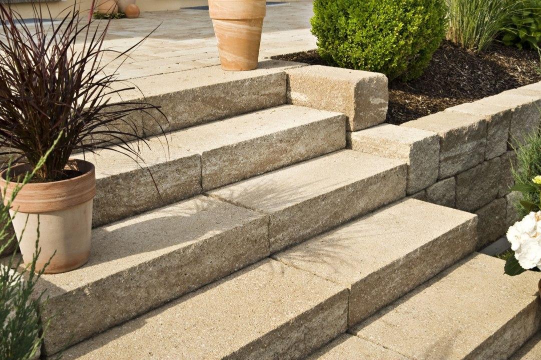 Treppenstufe Blockstufe KLASSIKLINE von GODELMANN Gepflastert Terrasse unn Steinmauer in Sandsteinoptik mit gepflasterter Treppe aus Blockstufen in Sandsteinoptik und Blumen und Wiese und bepflanztem Rindenmulchbeet udn gruene