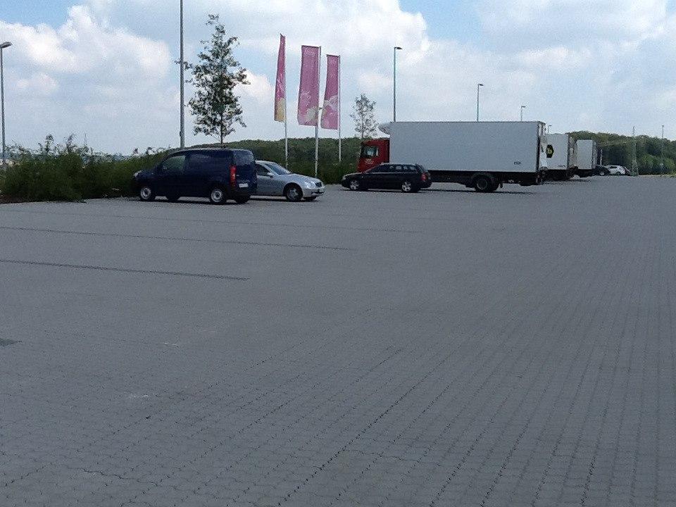 Pflasterstein GOWITEC von GODELMANN Gepflasterter Parkplatz in hellgrau mit Pflastersteinen und geparkten Autos Autos und LKW´s und Fahnen und Wiese und Graesern und Himmel