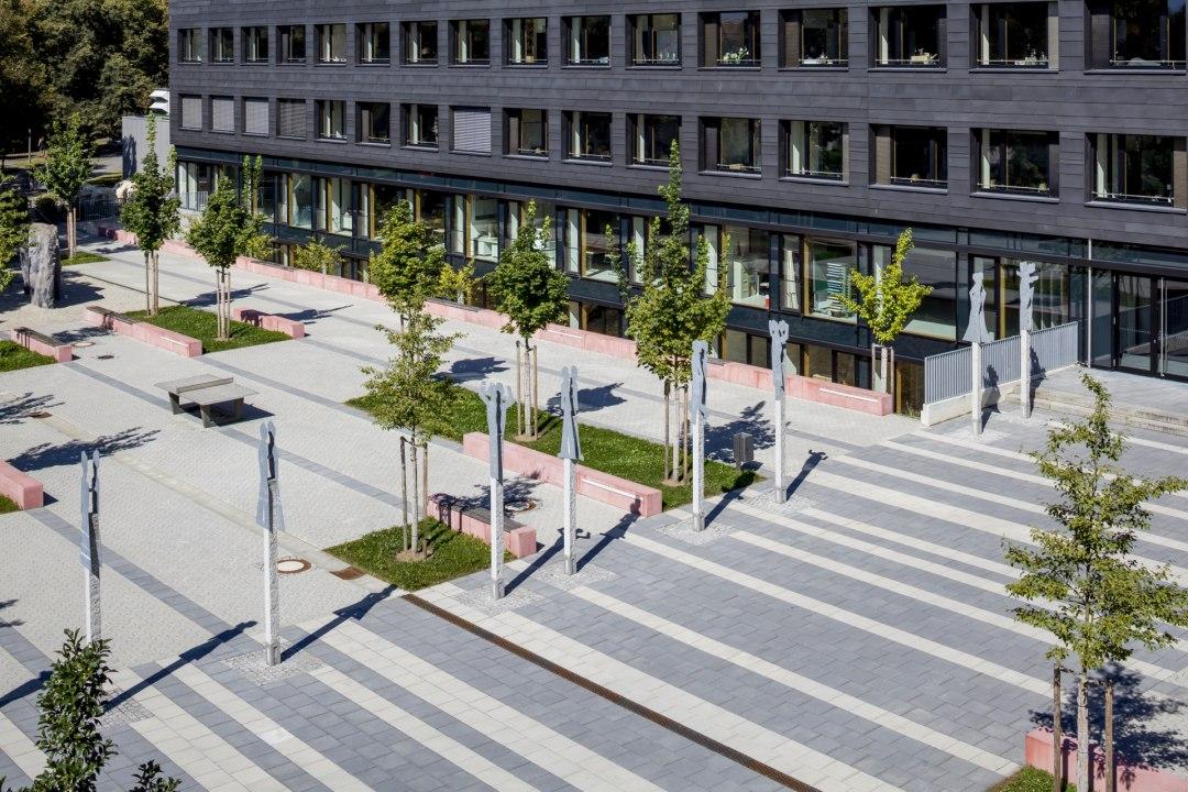Hellgrau gepflasterter Parkplatz und Hof mit Pflastersteinen in dynamischer Optik und roten Sitzbaenken und Baumen und Wiese und Strasse und Gebaeude und Haus mit Fenstern und Abfalleimern und Terrasse und Stuehle und Tische und Schirme