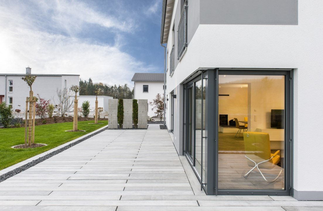 Grau gekalkt gepflasterte Terrasse mit Dielen vor weißem Haus und Kieselbeet und dunklen Tuerrahmen und Wiese und Baeumen und Raumteiler aus Sichtbeton und gelber Sessel und Fernseher im Haus und Himmel