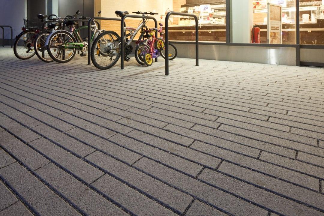 Fahrradstaender mit laenglichen grauen Steinplatten und Split in den Zwischenraeumen und Fahrraedern und beleuchtetes Geschaeft