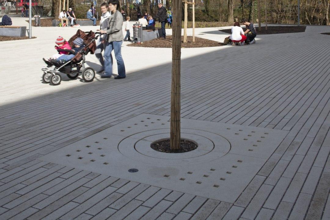Vorplatz mit laenglichen grauen Steinplatten und grauer Baumscheibe und Fußgaengern