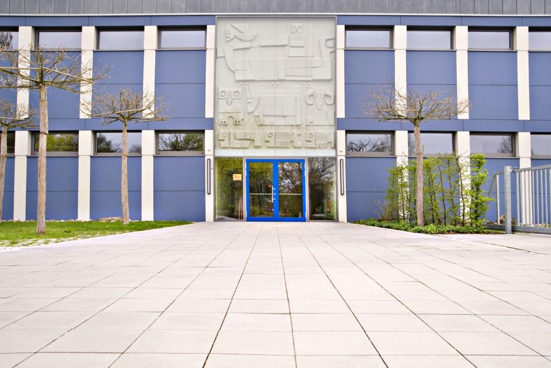 Vorplatz aus beigen quadratischen Steinplatten vor blauem Gebaeude mit blauer Tuer und Baeume und Wiese