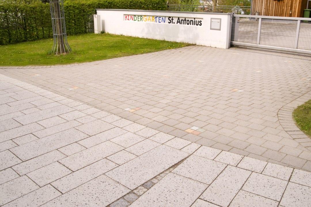 Einfahrt aus beigen und sandsteinfarbenen Steinplatten mit gestrahltem Muster und kleinen grauen quadratischen Steinplatten und Einfahrtstor und Baum und Wiese und Himmel