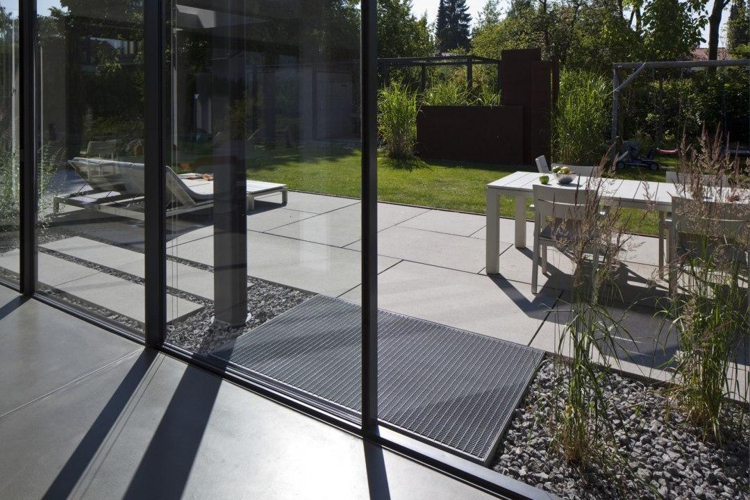 Terrasse aus grossen laenglichen hellgrauen Steinplatten aus Beton und Glastueren und Liegestuehle und Stuehle und Tisch und Steinplatten als Gehweg mit Kieselsteinen umrandet und Pflanzen und Rasen