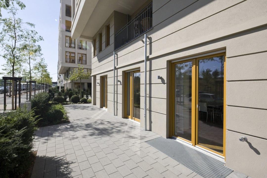 Steinboden aus grauen Steinen aus Beton und Haus mit großen Fenstern mit hellbraunen Fensterrahmen und Baeume und Sonnenschein
