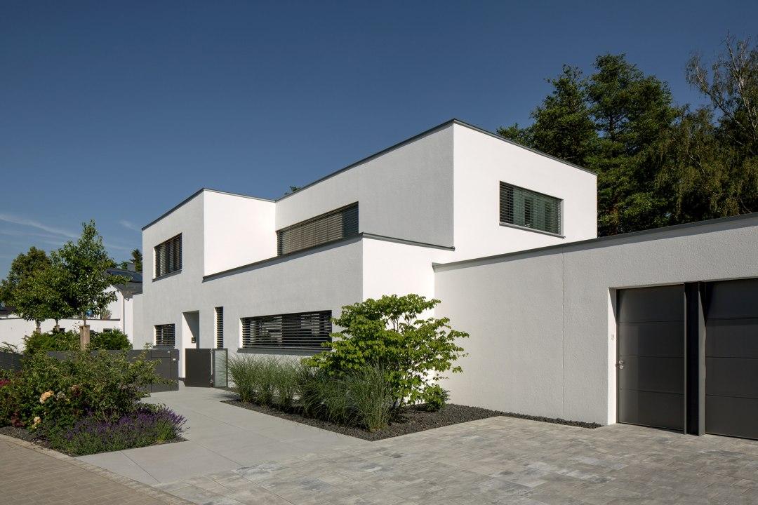 Gepflasterte Einfahrt in grau schwarz vor weißem Haus mit dunklen Fensterrahmen und Tuerrahmen und Hauseingang und bepflanztem Vorgarten Haus und Jalousienen vor Fenstern und Garage