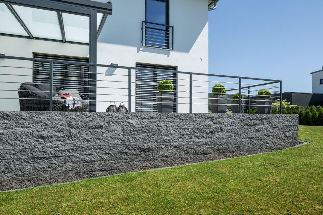 Steinmauer aus dunklen Steinen in Schieferoptik mit Edelstahlgelaender und gruener Wiese