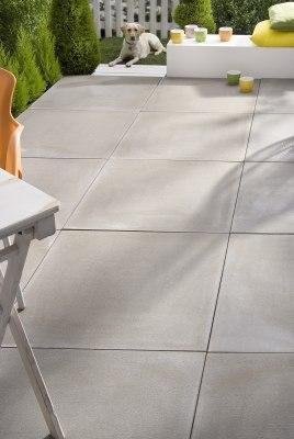 Grau gepflasterte Terrasse mit Steinplatten und Tisch und orangem Stuhl und weiße mauer mit bunten Teelichtern und Kissen und Hecke und weißer Zaun und Hund
