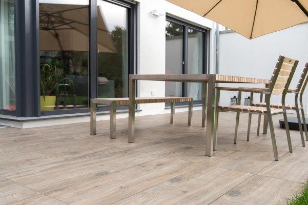 Gepflasterte Terrasse aus großformatigen Feinsteinzeugplatten in 120x40 cm in Natur Eichenoptik vor weißem Haus mit dunklen Tuerrahmen und Tisch und Sitzbank und Stuehlen und Schirm und Pflanze