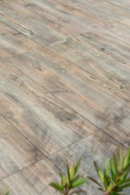 Gepflasterter Steinboden aus großformatigen Feinsteinzeugplatten in 120x40 cm in dunkler Eichenoptik und Pflanze