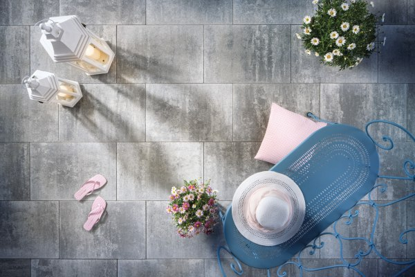 Gepflasterter Steinboden in grau schwarz mit rosa  Flip Flops und Blumen und Laternen mit Kerzen und Sonnenhut und blauer Bank und rosa Kissen auf dem Steinboden