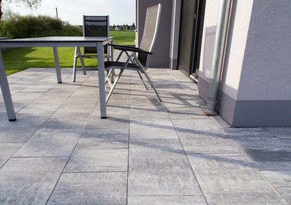 Gepflasterte Terasse in grau schwarz mit grauem Tisch und grauen Stühlen und Wiese vor weißem Haus mit offener Terrasentuer und Regenrohr