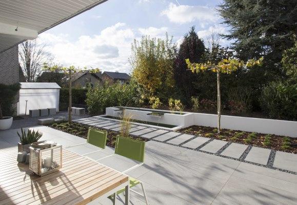 Terrassenplatte Gepflasterte Terrasse aus großformatigen Feinsteinzeugplatten und Terrassenplatten aus 120x40 cm mit Tisch mit Dekoration und Pflanze und gruenen Stuehlen und gepflasterter Terrassenweg mit Kieselsteinen