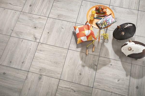 Gepflasterter Steinboden mit Terrassenplatten in großformatigen Feinsteinzeugplatten Carmino in 60x60 cm in grauer Eichenoptik mit buntem Kissen mit Tisch mit Magazin und Glaeser mit Orangensaft und Stiften und Springseil und  Sitzgelegenheiten