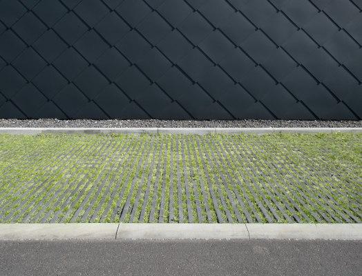 Graue Rasenplatten mit Rasenliner mit Gras in den Zwischenraeumen und mit Kieselsteinen und gepflastertem Steinboden umrandet vor Haus mit schwarzer Wandverkleidung