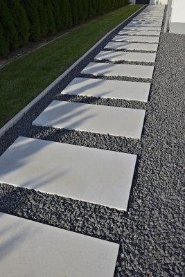 Gepflasterter Weg Massimo light aus Terrassenplatten 200x100 aus Sichtbetonin dunkelgrau mit grauen Steinen in den Zwischenraeumen  und Wiese und Hecke und Schattenwurf