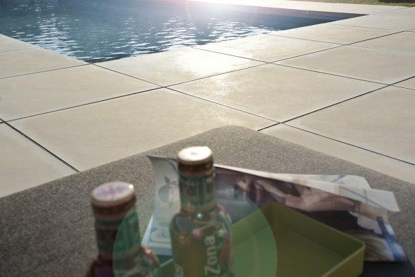 Gepflasterte Poolumrahmung Massimo light aus Terrassenplatten 100x100 aus Sichtbeton in dunkelgrau und Tisch mit Getraenken und offenem Magazin und Sonnenschein