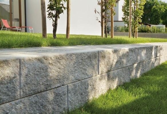 Steinmauer aus Plasterteinen fuer Gartenmauer in grau fuer massives Mauer und Stuetzwandsystem mit bruchrauen Sichtflaechen Grau und Wiese und Liegestuehle und Baeume mit Baumstuetzen