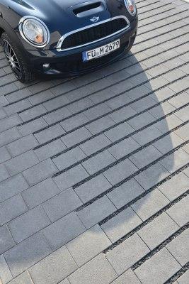 Rasenfugenstein NUEVA Rasenliner von GODELMANN Gepflasterter Parkplatz und Eingang und Einfahrt mit anthrazit Rasenliner mit Basaltsplitt und geparktem schwarzen Auto und Mini und Schattenwurf