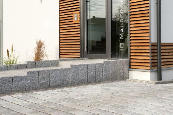 Gepflasterter-Hauseingang-dunkelgraue-Einrahmung-Glastuere-weißes-Haus-Holzzaun