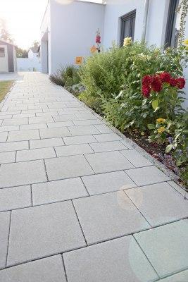 Gepflasterter Weg aus grauen Pflastersteinen im Reihenverband und bepflanztes Blumenbeet an Hausmauer und weißes Haus und Wiese und dunkle Fensterrahmen
