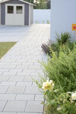 Gepflasterter Weg aus grauen Pflastersteinen im Reihenverband und bepflanztes Blumenbeet und Wiese und Gartenhaus in grau mit weißen Tueren