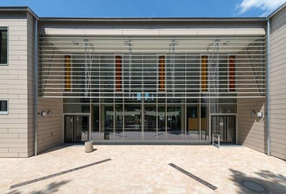 Gepflasterter Vorplatz in grau schwarz und braun beige vor Gebaeude mit Glasfassade und orangen Fenstern und Edelstahlverkleidung auf Haus und Tueren und Abfalleimer