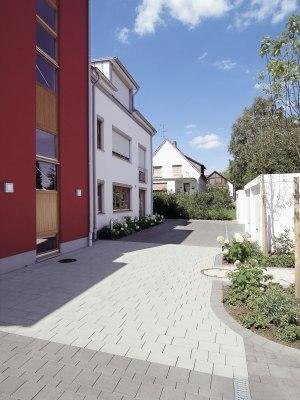 Gepflasterter Hauseingang in hellgrau vor weißem Haus mit roter Hauswand und Fenstern und Jalousie und bepflanztes Blumenbeet und weißen Garagen mit weißen Garagentoren