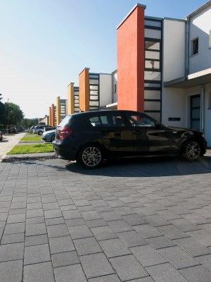 Gepflasterte graue Einfahrt und Parkplaetze vor Haeusern mit Autos und bunten Hauswaenden udn Glasfassade und Himmel und Pflanzen