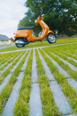 Graue Rasenplatten mit Rasenliner mit Gras in den Zwischenraeumen und orangen Roller und Haus und Baum und Himmel