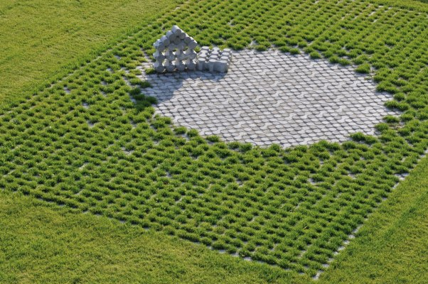 Rasenkammerstein in hellgrau mit Gras in Zwischenraeumen als Pflasterplatte verlegt mit gepflastertem Kreis aus Rasenkammersteinen und Fuellsteinen und gestapelten Rasenkammersteinen und gruene Wiese