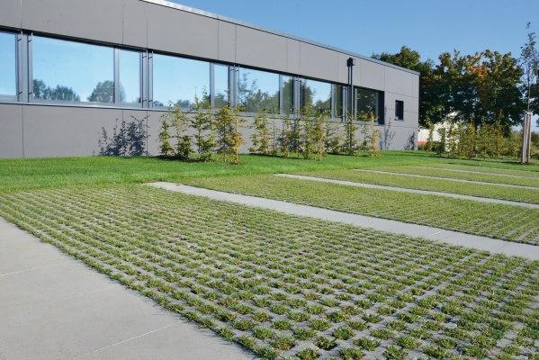 Graue Rasengitterplatten mit grossen geraeumigen Rasenkammern mit Gras bepflanzt als Parkplatz und Parkmoeglichkeit für PKW´s vor grauem Haus mit langer Fensterfront und Baeumen und gruener Wiese und Himmel