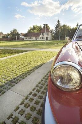 Graue Rasengitterplatten mit grossen geraeumigen Rasenkammern mit Gras bepflanzt und Verwendung als Parkplatz und Parkmoeglichkeit fuer Autos und hellgrau gepflasterte Steinplatten abgegrenzt und weißes Haus mit Holzverkleidung und roter Oldtimer