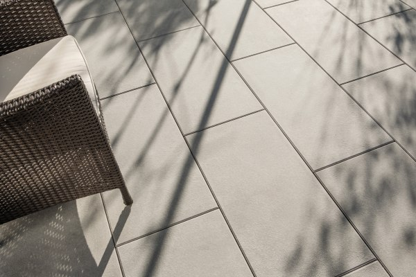Terrassenplatte - Gepflasterter Steinboden in dunklem sandgrau und Stuhl mit Kissen