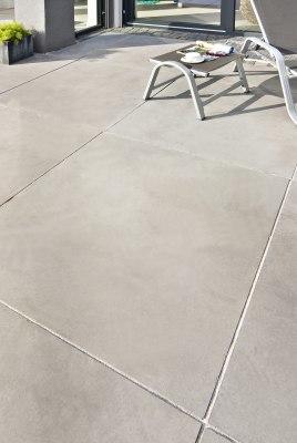 Gepflasterte Terrasse Massimo light aus Terrassenplatten 200x100 aus Sichtbeton in hellgrau mit Liegestuhl und Tisch mit Sonnenbrille und Kaffeetasse und Magazin und bepflanzter Blumentopf