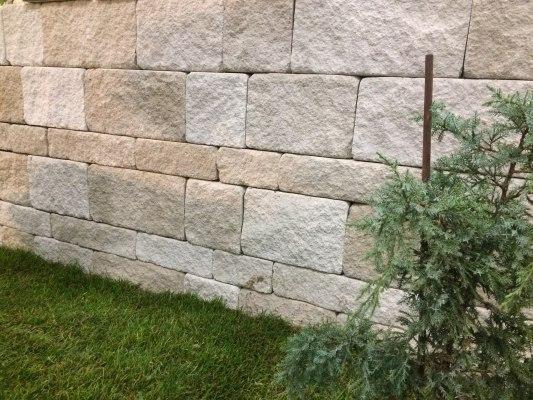 Gepflasterte Steinmauer aus Kalkstein und Gras und Baum und Holzstock