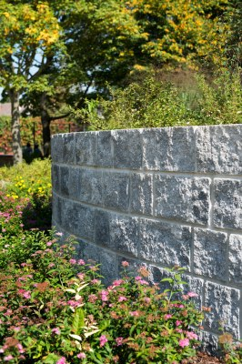 Gepflasterte Steinmauer in grau schwarz mit halbrund gepflasterter Mauer mit bepflanztem Blumenbeet und Baeumen
