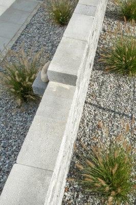 Gepflasterte Steinmauer in grau schwarz im Wechselmauerwerk und bepflanzte Kiesbeete mit Graesern und großem weißen Stein