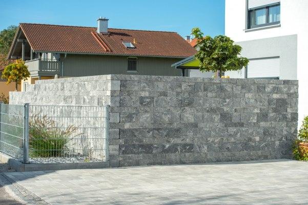Gepflasterte Gartenmauer in grau schwarz im Schichtenmauerwerk und Kieselsteinen und Pflanzen in Kiesbeet und gepflasterte hellgraue Hofeinfahrt vor weißem Haus und Baeume und Haus im Hintergrund