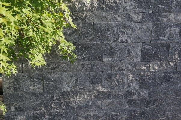 Gepflasterte Steinmauer in grau schwarz im Schichtenmauersystem mit Pflanzen