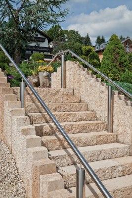 Gepflasterte Treppe in Sandstein-Beige Optik mit silbernem Edelstahl Treppengeländer und Blumen und Baum und Haus