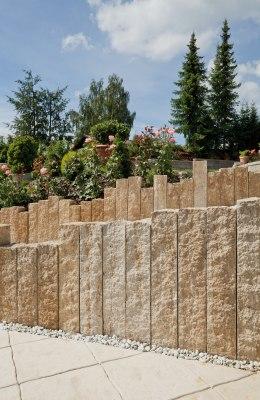 Gepflasterte Wegeinfassungen mit Treppenanlage udn gepflasterter Einfahrt mit weißen Kieselsteinen mit Wiese und Rosen und Baeumen