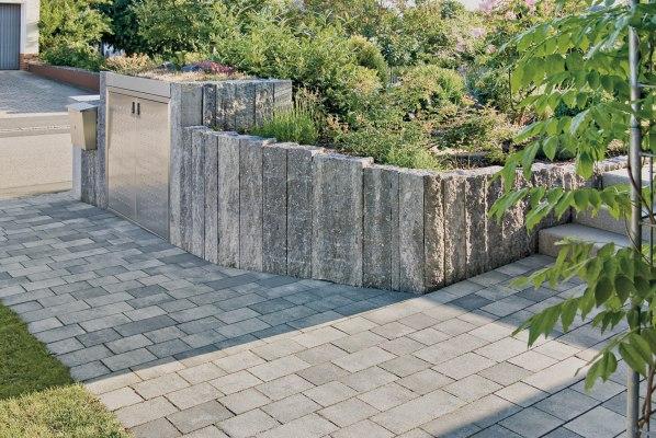 Gepflasterter Hauseingang und Einfahrt mit Steinmauer in grau-schwarz nuanciert als Wegeinfassungen und Treppenanlage mit gepflasterten Treppen und Edelstahl Briefkasten und Wiese und bepflanztem Rindenmulchbeet