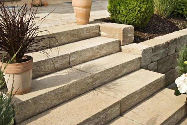 Gepflasterte Terrasse aus beigem Sandstein und Treppen aus Blockstufen in Sandsteinoptik mit bepflanztem Blumentop und Rindenmulchbeet